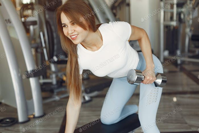 A beautiful girl is engaged in a gym with a dumbbells