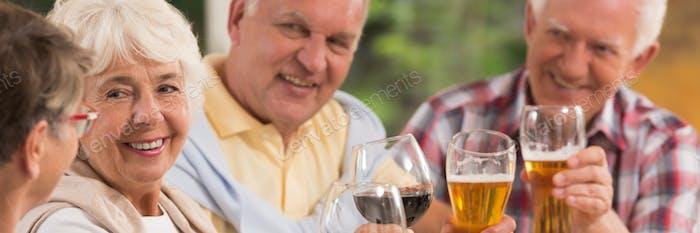 Elderly friends toasting a drink
