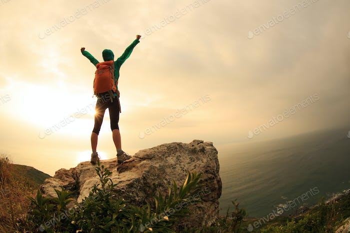 Happy on sunrise seaside cliff edge