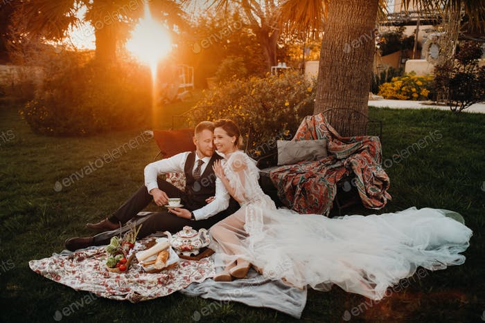 Abendessen das Brautpaar auf dem Picknick.Ein Paar entspannt bei Sonnenuntergang in Frankreich.Braut und Bräutigam auf einem