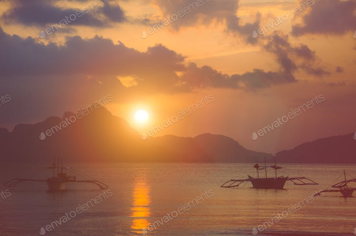 Sunset at El Nido. Banca boat anchored in a bay. Palawan island, Philippines