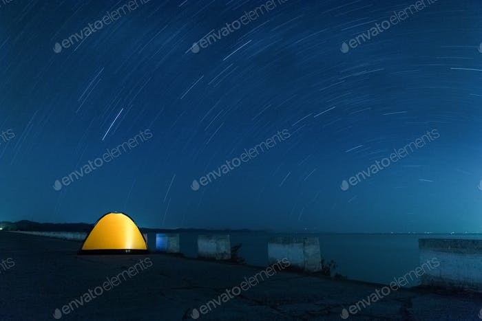 star trails and tent, long time exposure, beautiful starry sky landscape