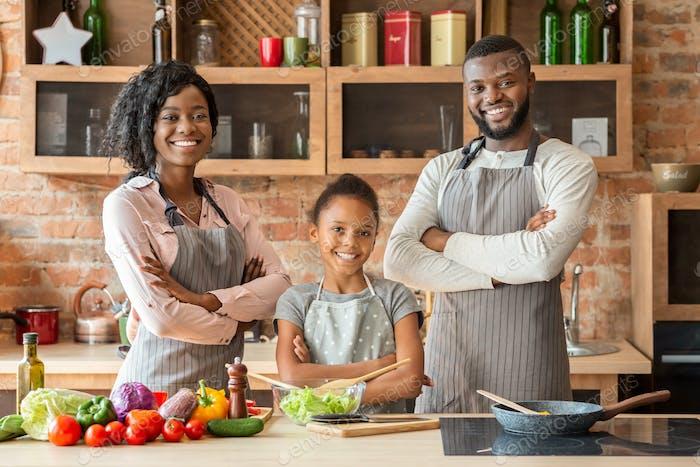 Erfolgreiche Familie in Schürzen posiert über Küchenhintergrund