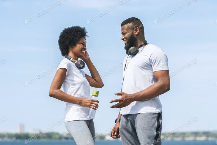 Man And Woman Talking After Morning Jog Near River
