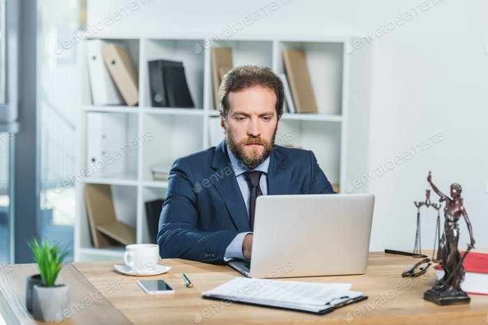 portrait of concentrated lawyer working on laptop at workplace with documents in office