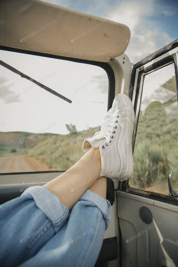Feet on the dashboard of a jeep.