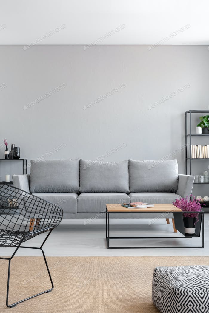 Real photo of a simple living room interior with a grey sofa, ar