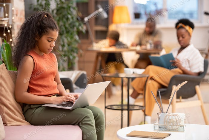 Serious African schoolgirl with laptop on her knees preparing home assignment