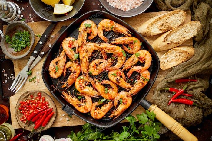 Leckere appetitlich geröstete Garnelen mit Gewürzen auf Pfanne mit Zutaten auf rostigem Hintergrund