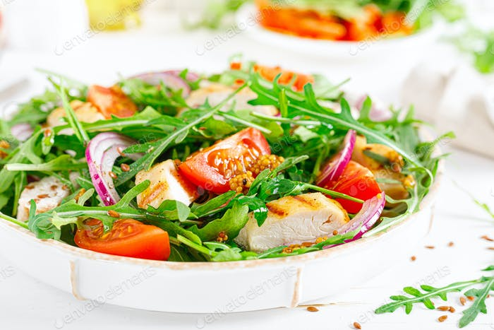 Fresh vegetable salad with grilled chicken fillet, breast, tomato and arugula