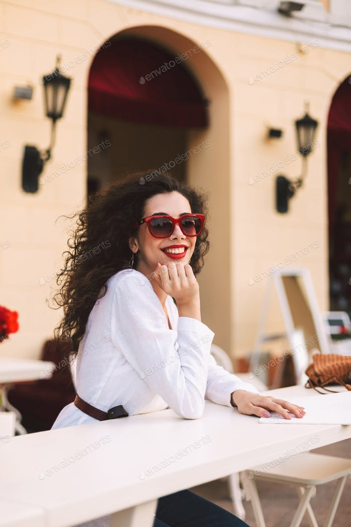 Beautiful smiling in sunglasses standing and happily looking in camera in summer terrace of cafe