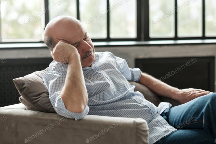 Senior hispanic confined man taking a nap in sofa at home