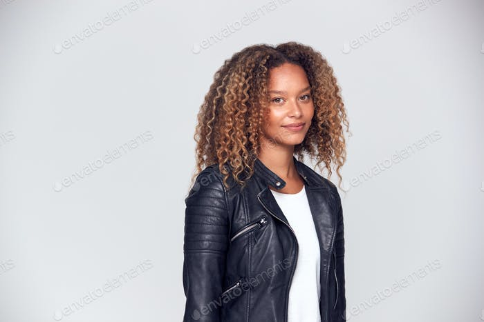 Waist Up Studio Shot Of Happy Young Woman Wearing Leather Jacket Smiling At Camera