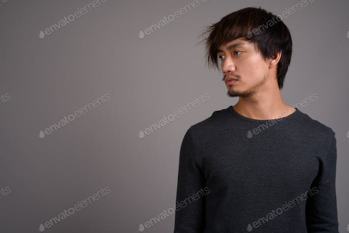 Young Asian man against gray background