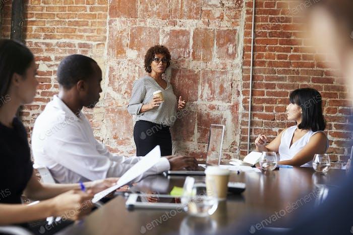 Зрелая деловая женщина, стоящая на заседании совета директоров