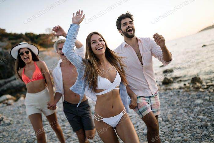 Cheerful friends enjoying weekend and having fun on beach