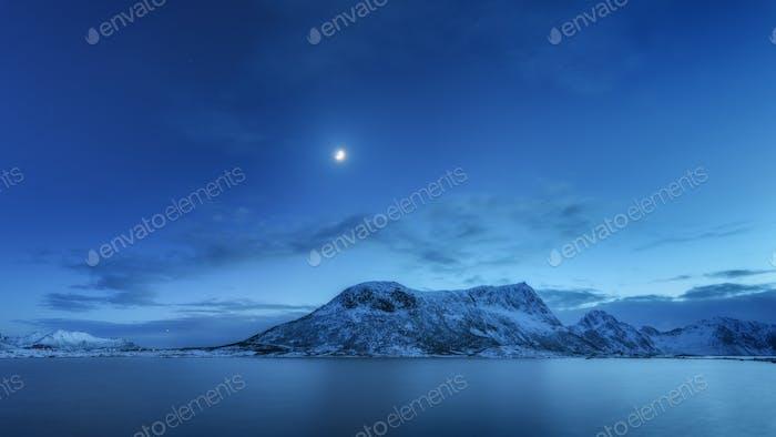 Montañas contra el cielo azul con nubes y luna en invierno