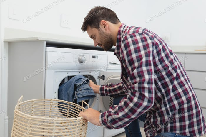 Side view of Caucasian man putting dirty clothes into the washing machine in a comfortable home