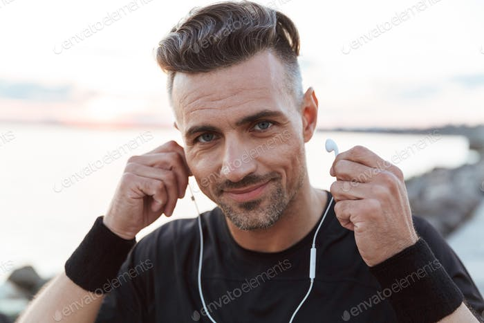 Close up portrait of a happy sportsman listening to music