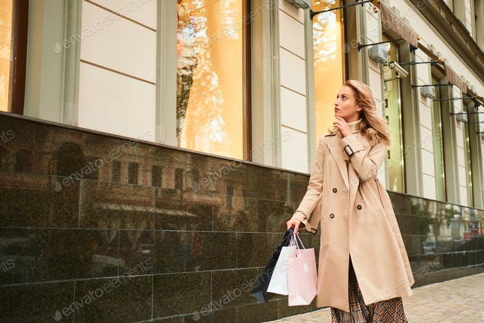 Beautiful stylish blond girl in beige coat with shopping bags thoughtfully walking on city street