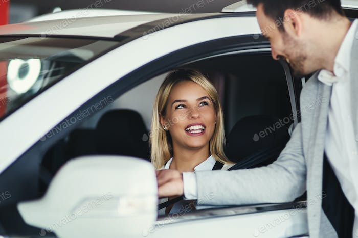 Woman is talking to handsome car dealership worker while choosing a car
