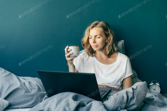 A woman is sitting in bed and typing on a laptop.
