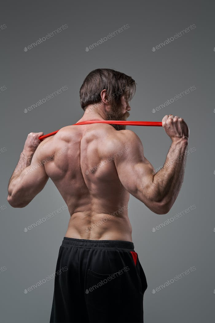Backview of successful sportsman with resistance bands in studio