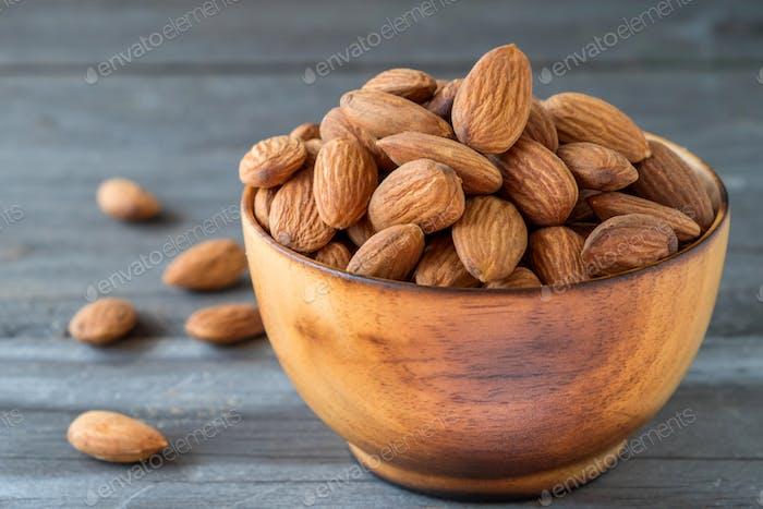 Almonds in wooden bolw on wooden floor.