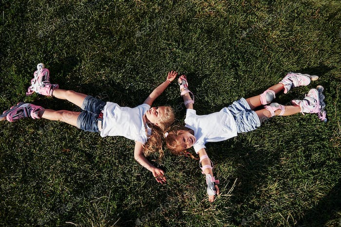 Top view. Feeling freedom. Two female kids lying on the green grass at summertime