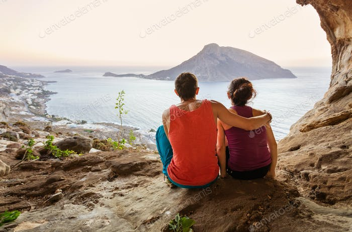 Couple of rock climbers having rest while sitting at bottom of cliff
