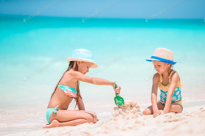 Two little happy girls have a lot of fun at tropical beach playing together