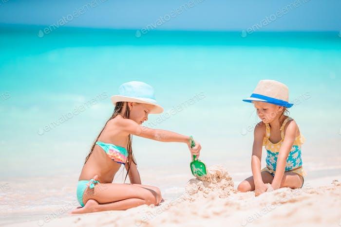 Zwei kleine glückliche Mädchen haben eine Menge Spaß am tropischen Strand spielen zusammen