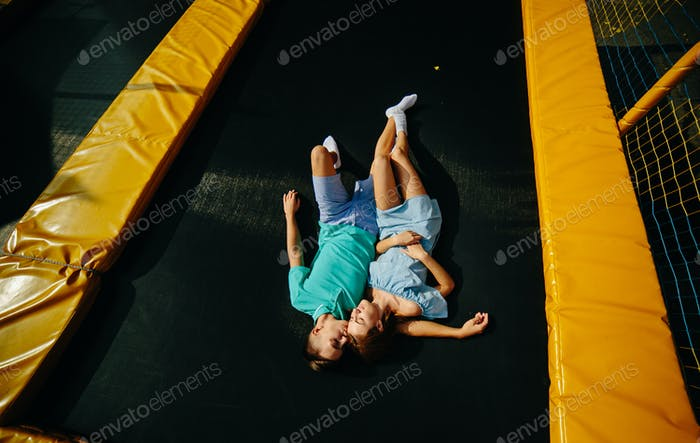 Couple lie on trampoline in the park