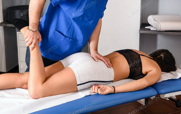 Male osteopath treating the knee of a patient