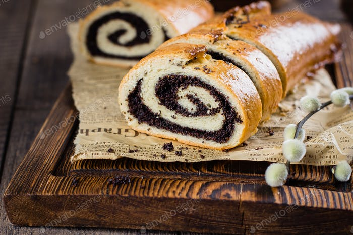 Homemade roll with poppy seeds on wooden board on wooden table background.