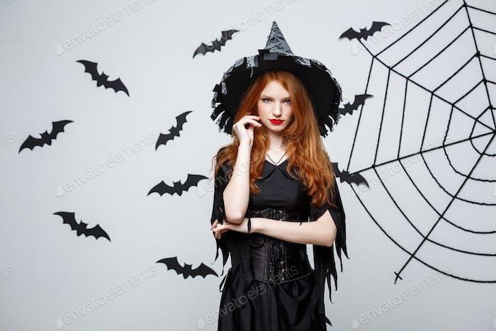 Halloween Hexe Konzept - Halloween Hexe hält posiert mit ernstem Ausdruck über dunkelgrau