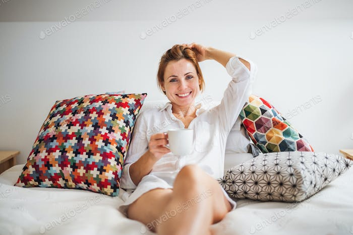 Young woman with night shirt sitting indoors on bed in the morning, holding cup.