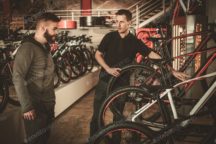 Thumbnail for Salesman showing a new bicycle to interested customer in bike shop.