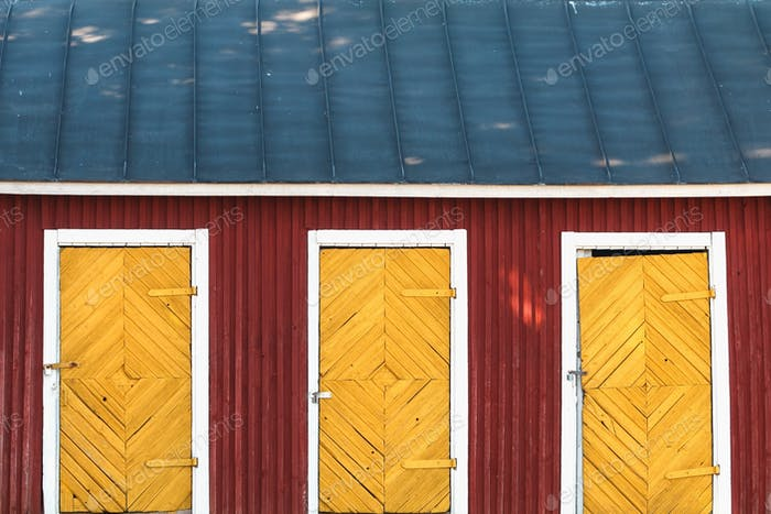 Three vintage yellow doors in a red wooden house with blue roof. Scandinavian design.
