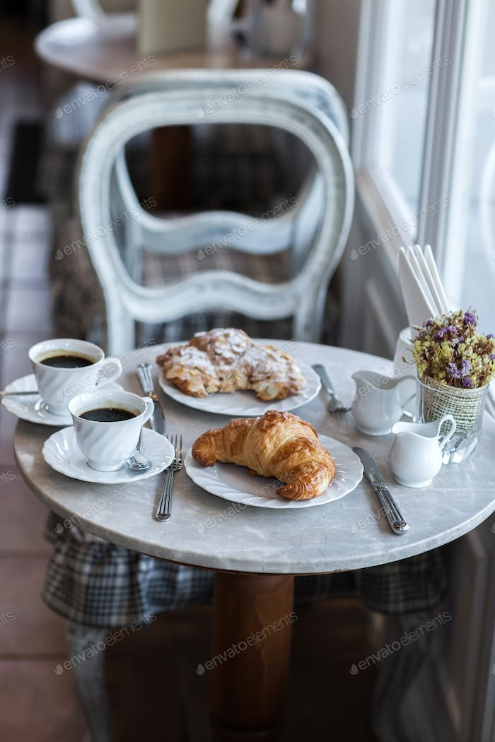 Frehcn breakfast with fresh croissants and hot coffee on white table