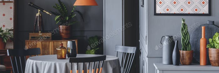 Close-up photo of dining table with vases and fresh plants and v