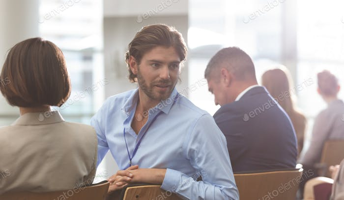 Businessman interacting with his colleague during seminar in office building
