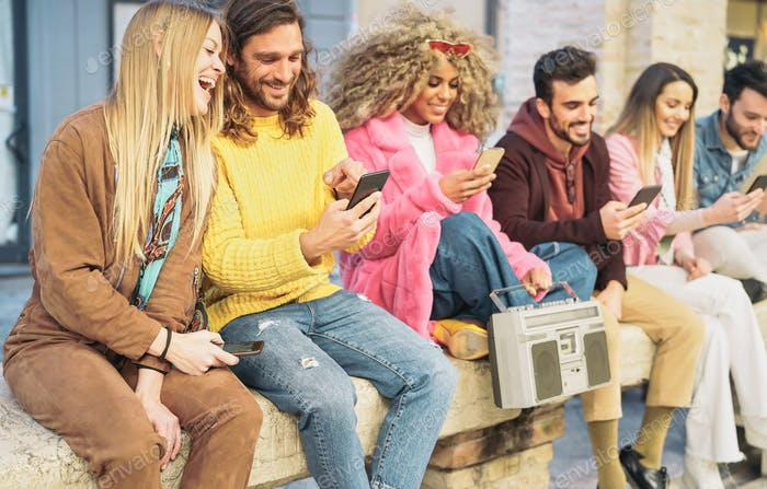 Group happy friends using mobile smartphones in the city