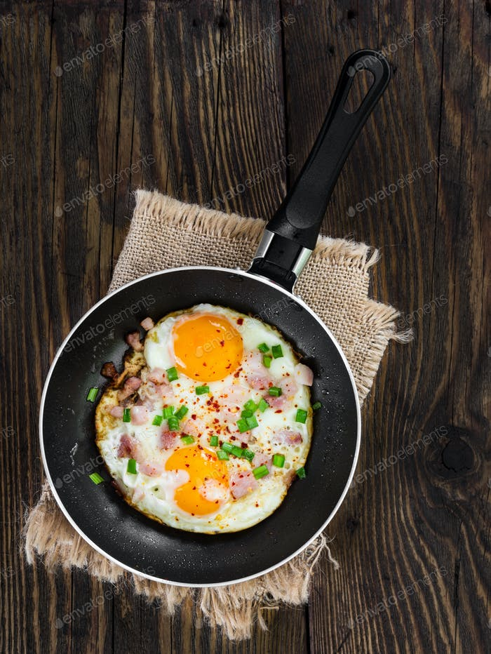 Fried eggs with ham and onion in pan