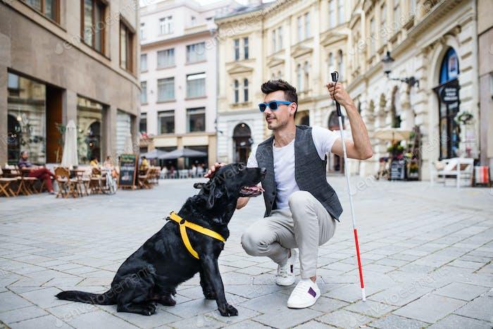 Junger Blinder mit weißem Stock und Blindenhund auf Sockel Zone in der Stadt