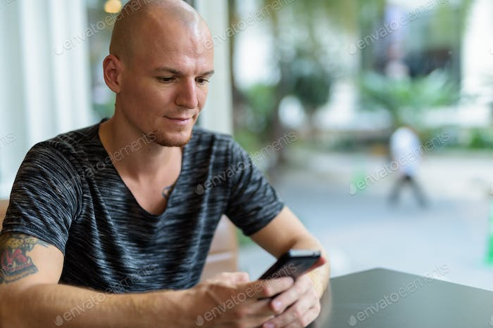 Young handsome bald man using mobile phone inside restaurant wit