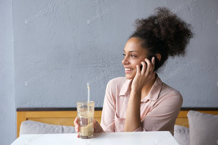 Woman sitting at restaurant talking on mobile phone