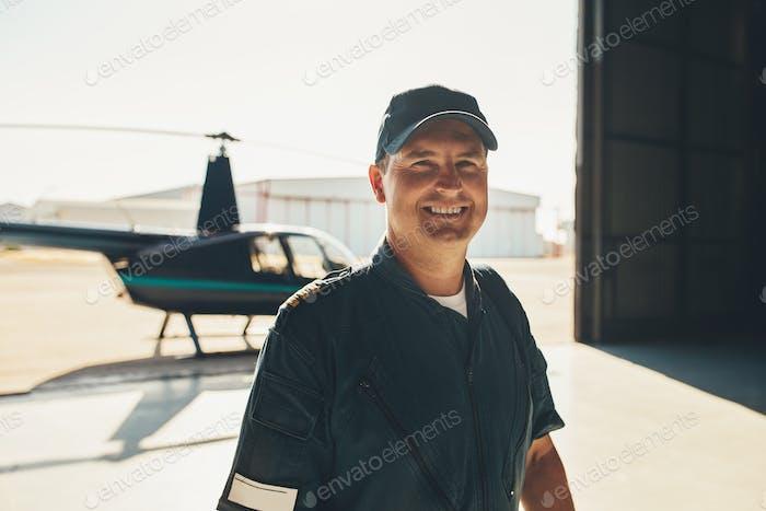 Glückliche männliche Pilot stehend im Flugzeughangar