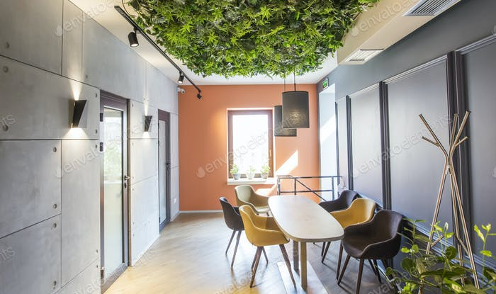 Cozy corner in empty cafe or coffee shop with green plants ceiling
