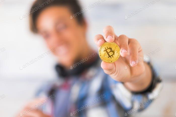 adolescente caucásico feliz mostrando bitcoin - tecnología de dinero futuro